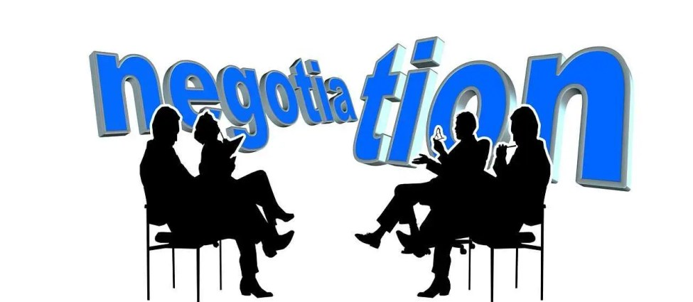 "The word ""negotiation"" behind the silhouettes of four people sitting with their legs crossed"