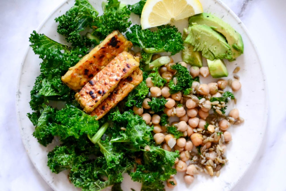 Vegan salads guaranteed to delight your tastebuds and fill you up fast! This chopped kale salad is drizzled with a fresh lemon vinaigrette and topped with sizzling grilled tempeh. #vegan #salad #recipes