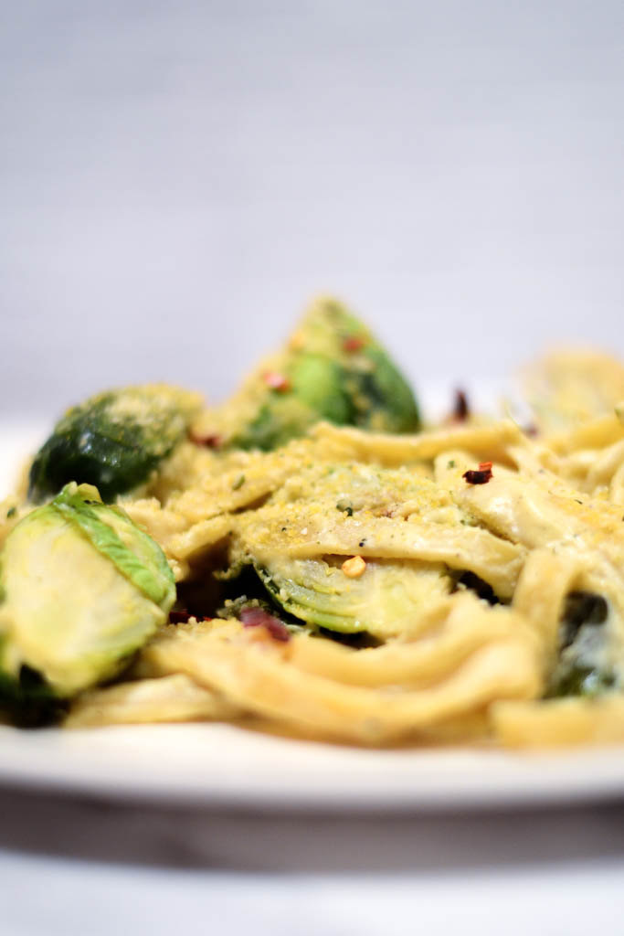 If you love to cook easy vegan pasta recipes you will fall in love with this creamy, garlicky fettuccini pasta! It blends perfectly with the crisp flavor of fresh white wine. Simply add roasted brussel sprouts and you have a quick and absolutely scrumptious weeknight dinner. #veganrecipes #veganfood