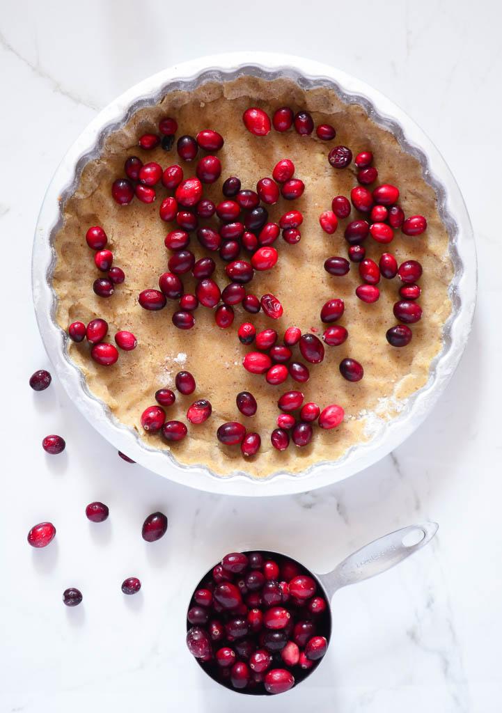 This recipe for the Ultimate Vegan Cranberry Custard Tart tastes perfectly refreshing and sweet. Bake it for your next holiday party, it's sure to be a crowd-pleaser! #vegancustardrecipe #vegancustardpie #vegancustardtart
