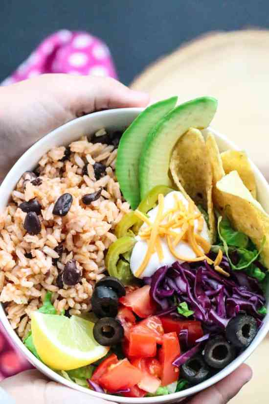 Two Hands holding white bowl with Mexican Rice and Black Beans and a variety of toppings.