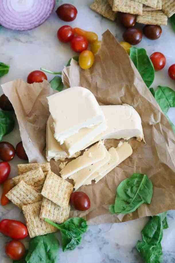 Overhead shot of broken and sliced vegan cheese with crackers and spinach beside.