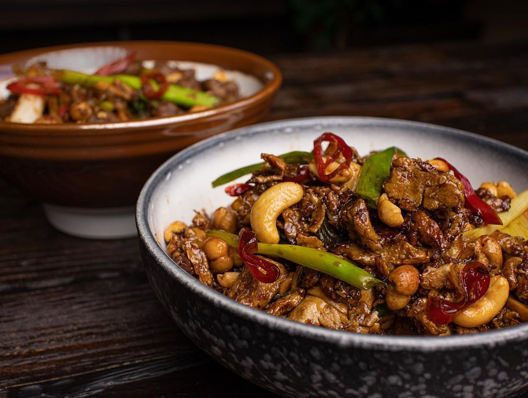 two versions of vegan kung pao chicken junk food and whole multip img 0 90e368b8