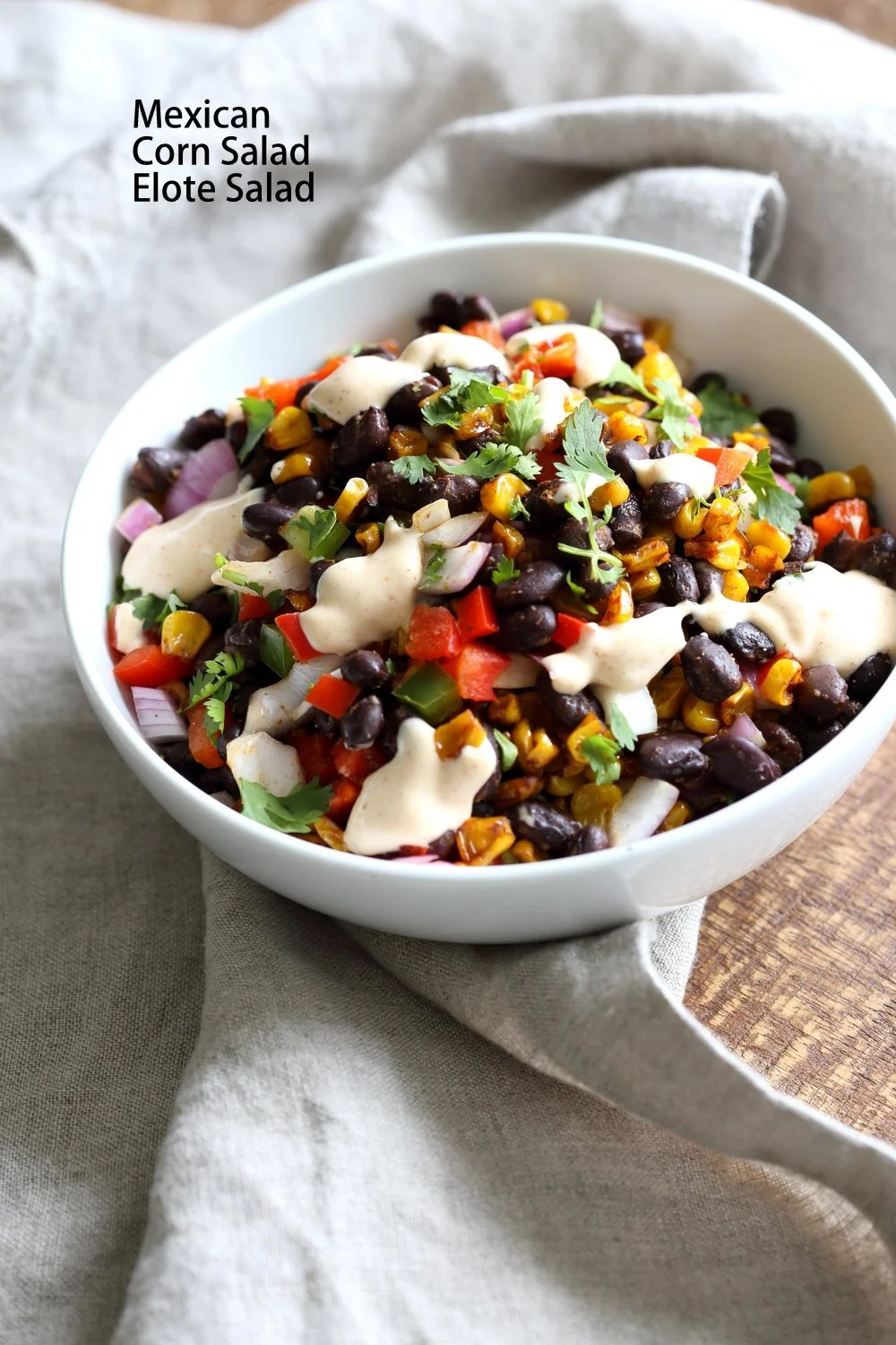 Mexican street corn salad in a white bowl with grey napkin
