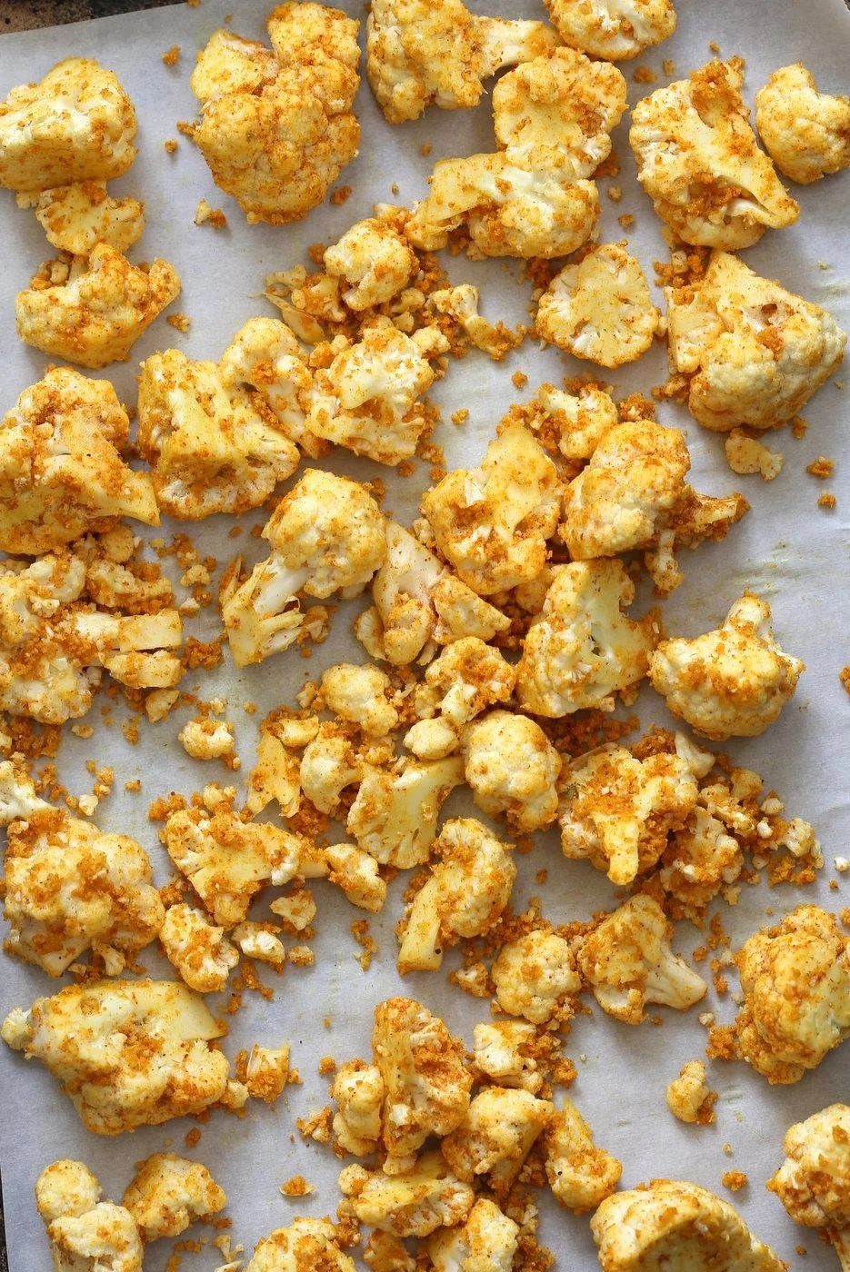 Roasted Cauliflower on Baking Sheet. Turmeric Roasted Cauliflower with Raita Dip. These Delicious Golden Cauliflower Bites are easy and quick. Serve with a dash of lemon or with a Yogurt onion dip or Green Chutney. #Vegan #Soyfree #Nutfree #veganricha #Recipe. Can be #glutenfree
