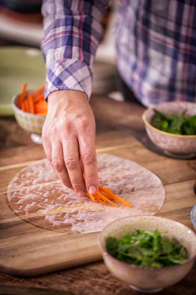 Picture of Man Rolling Vegan Spring Rolls on Wooden Cutting Board