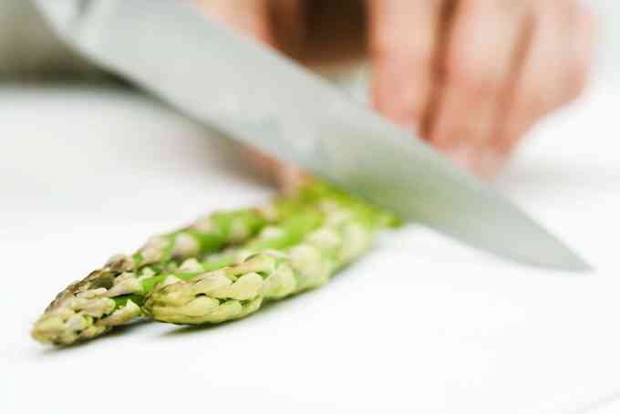 woman cutting asparagus with knife cropped view for asparagus salad