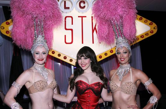 """Claire Sinclair and Showgirls at """"Welcome to STK"""" sign"""