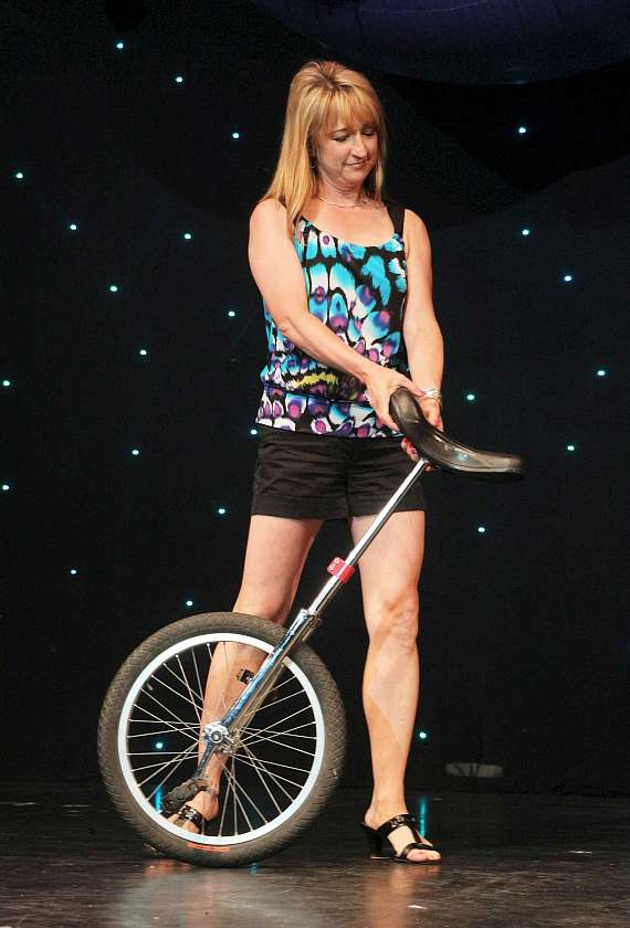 An audience member helps Jeff Civillico with a unicycle