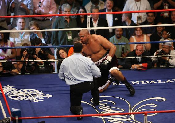 Jameel McCline tries to get up as referee Tony Weeks continues the count