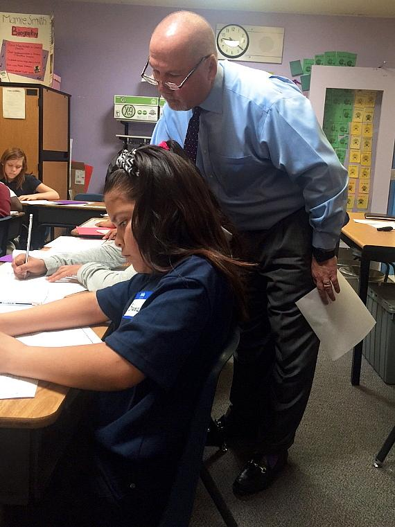 vada President of Bank of America, George W. Smith, helps a 4th grade student at J.E. Manch Elementary School with her area and perimeter lesson.