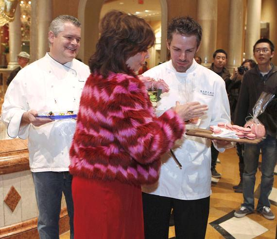 Rita tastes pink cookies from world famous Chefs Luciano Pelligrini and Mark Hopper