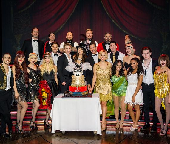 Cast poses with Cake for 100th Performance Celebration
