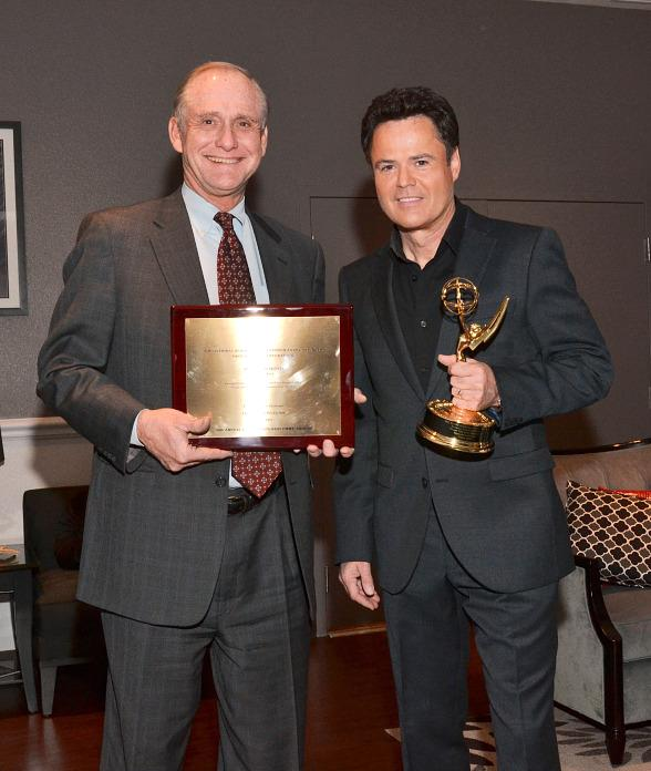 Tom Axtell, general manager of Vegas PBS, presents Donny Osmond with honorary Emmy Award
