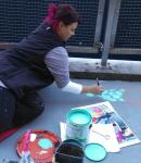 Artist from We Talk Chalk paints 3D drawing on the side sidewalk outside the store