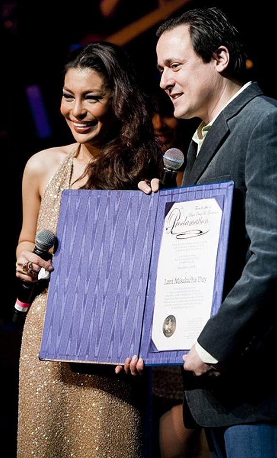 Angelo Giordano holds the Proclamation on stage with Lani Misalucha and cast members of Voices