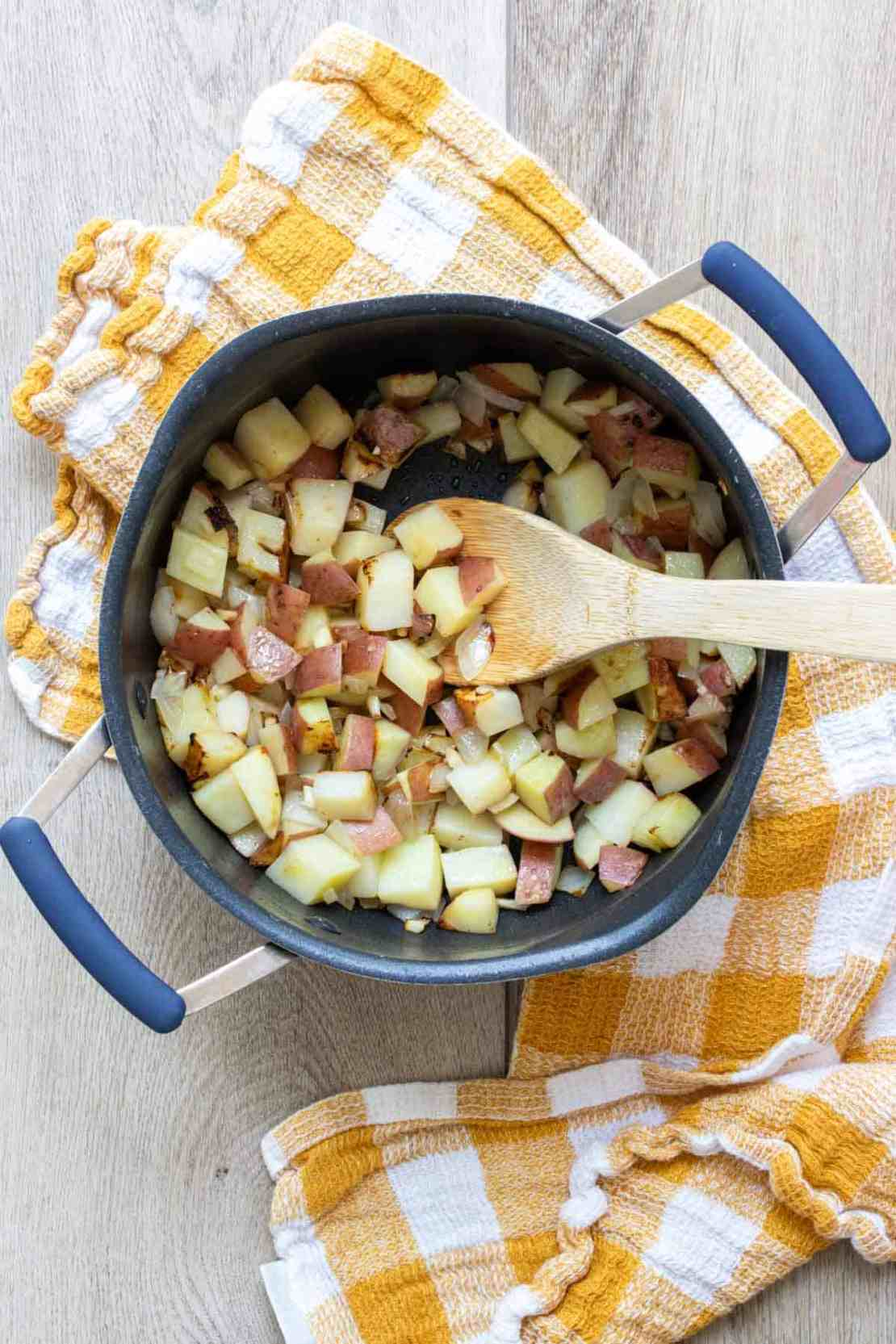 Wooden spoon mixing chopped potatoes in a pot