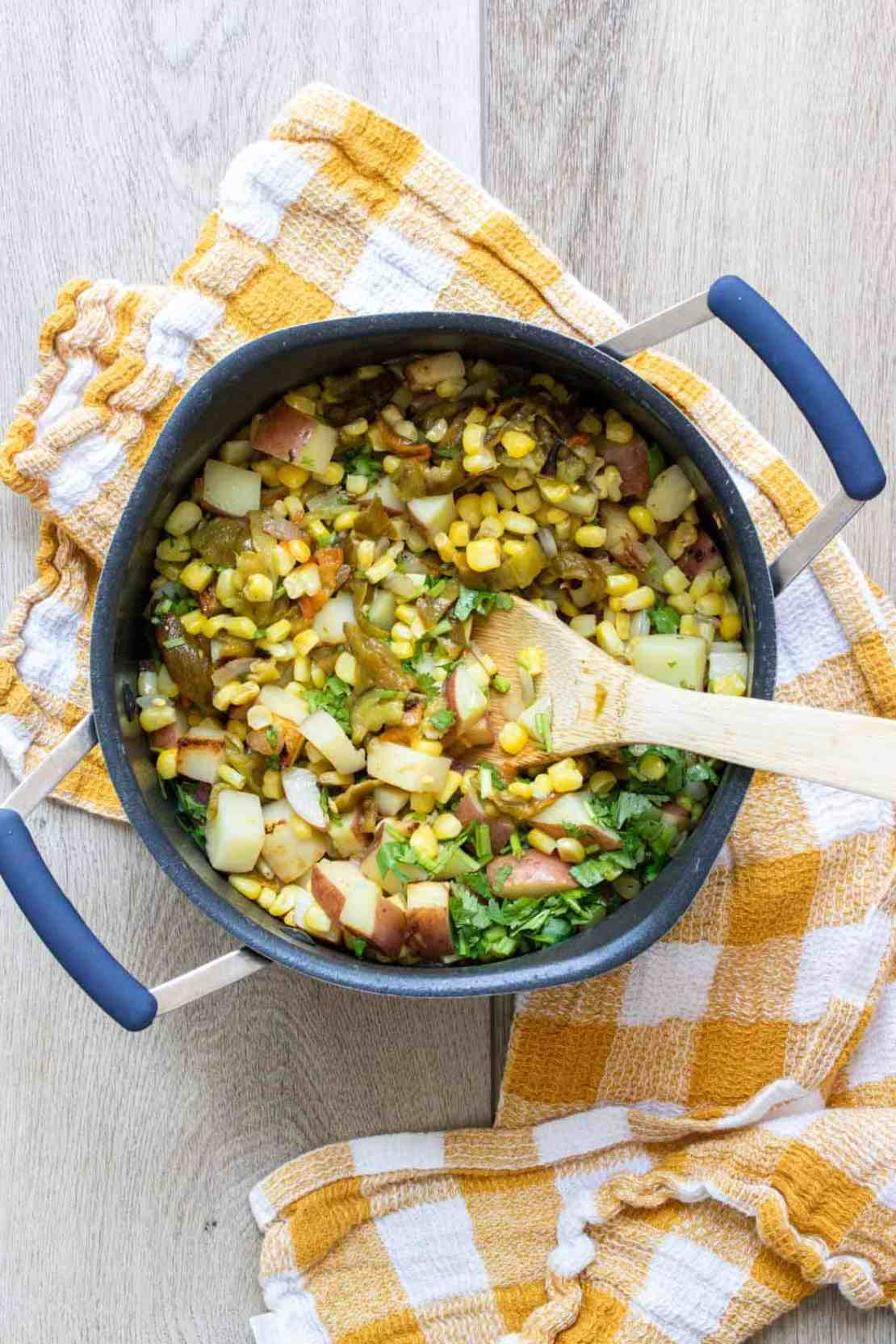 Wooden spoon mixing chopped potatoes, corn and peppers in a pot