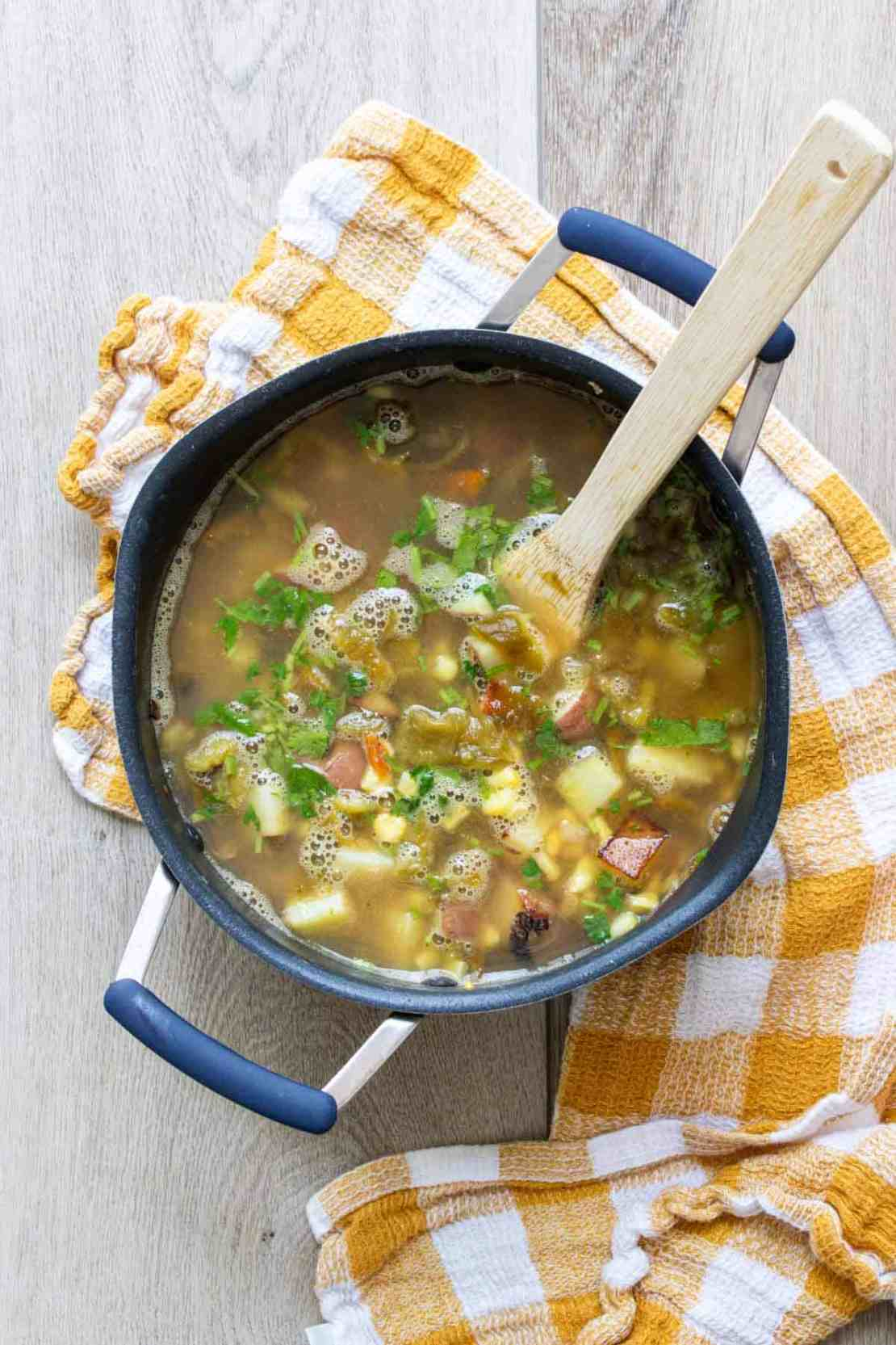 Wooden spoon stirring a veggie broth soup with herbs in a pot