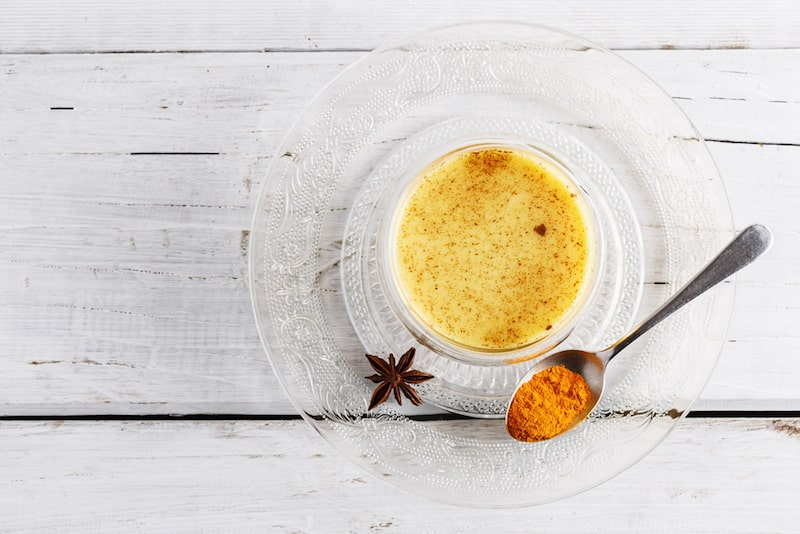 Top view image of turmeric latte over white wooden table with copyspace