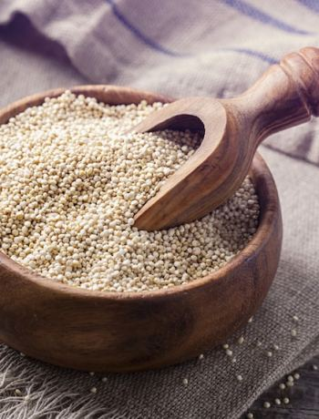 White quinoa seeds on a wooden background