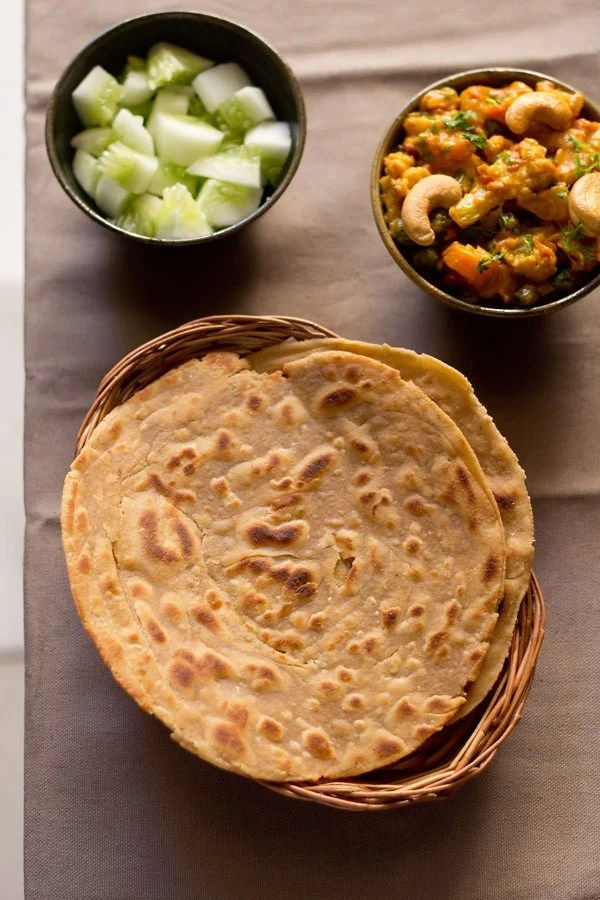 Lachha Paratha served in a cane basket with gravy dish and salad