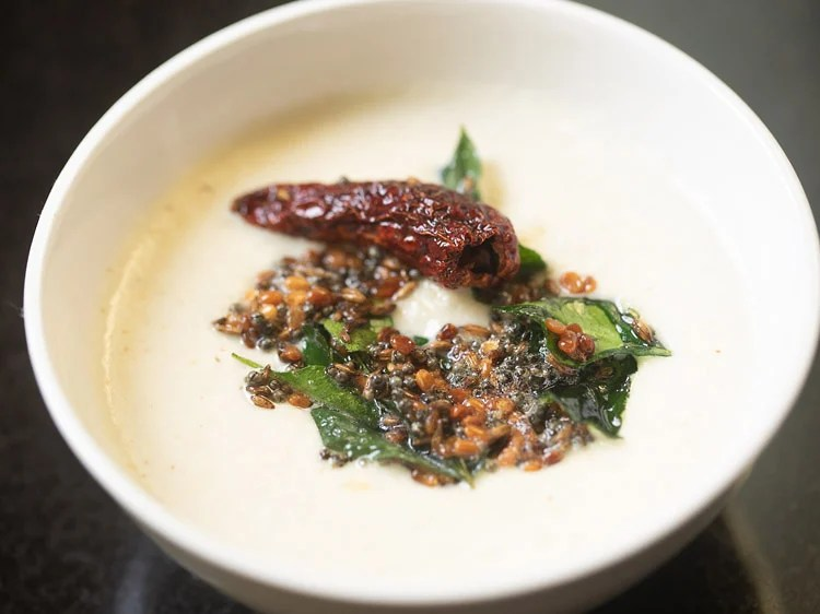 tempered spices and oil poured into white bowl with coconut chutney base