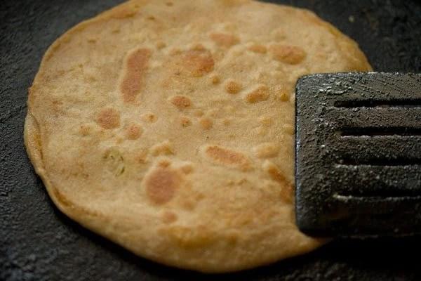pressing gobi paratha with a spatula