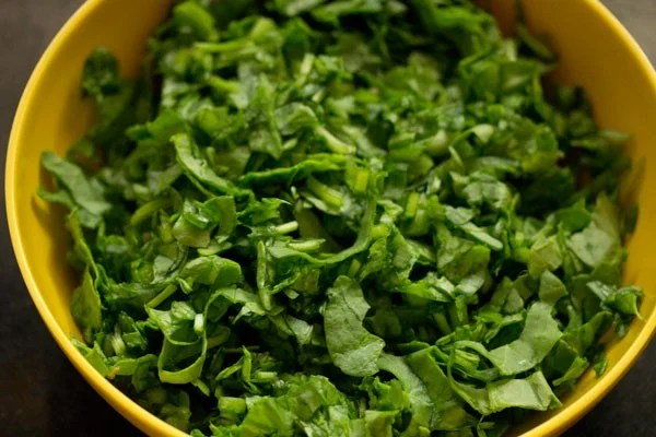 finely chopped spinach in a yellow mixing bowl