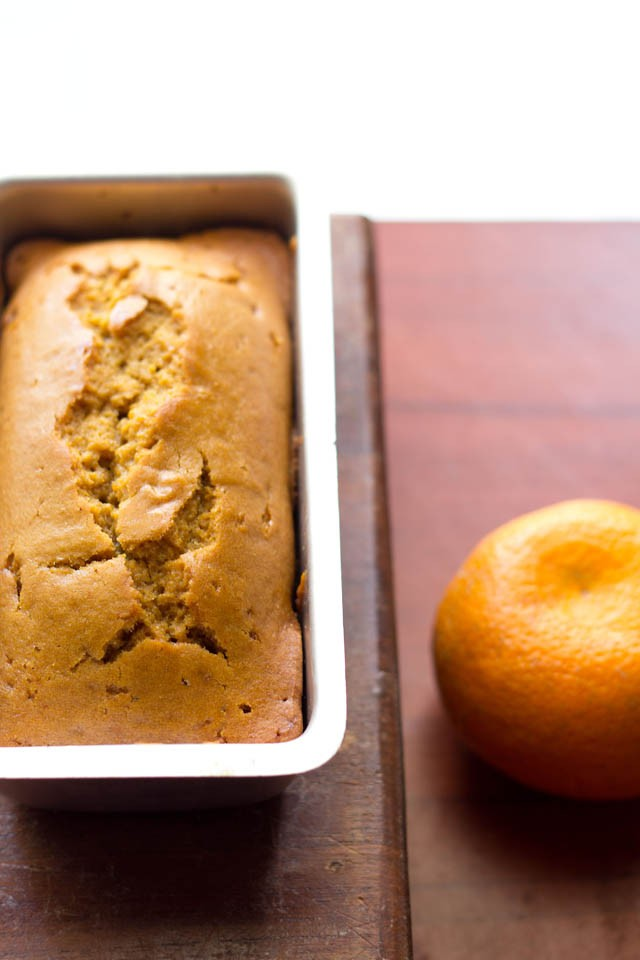 eggless orange cake in a loaf pan with a orange next to it on a brown table