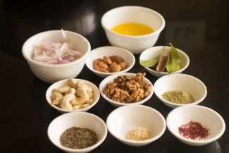 Ingredients for Kashmiri pulao recipe measured out in white bowls on a black table.