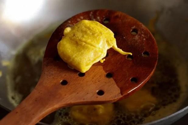 fried, crisp paneer pakora on a wooden slotted spoon