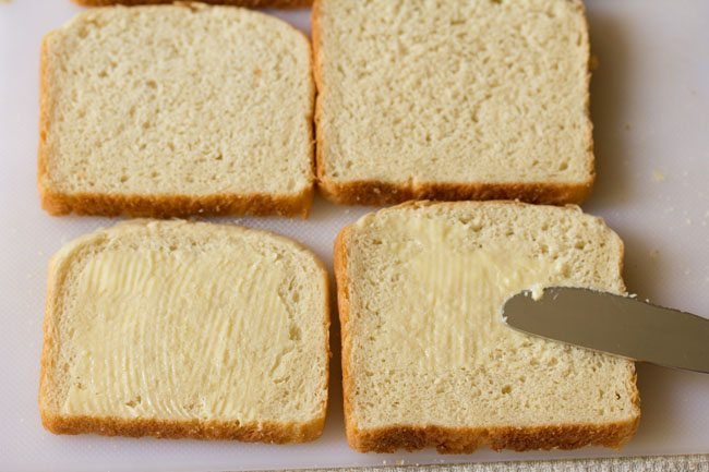 applying butter on bread slices on a board
