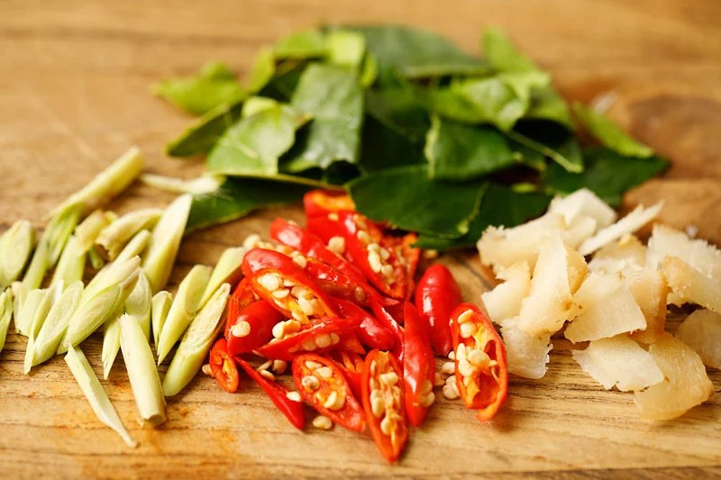 sliced lemongrass, Thai red chiles, galangal and torn kaffir lime leaves on a wooden cutting board