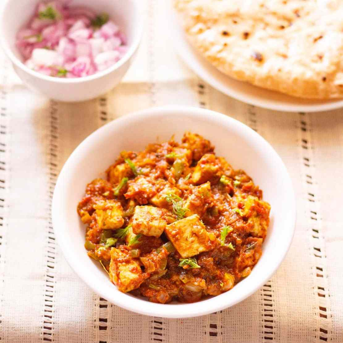 paneer tawa masala with coriander leaves garnish in a white bowl on a cream linen with a side plate of roti and a small side bowl of chopped red onions and coriander