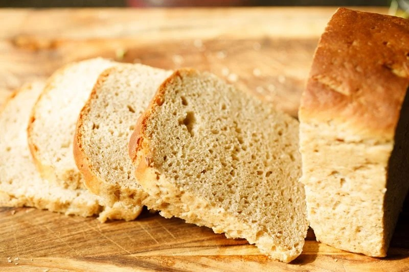 bread loaf being sliced on a wooden chopping board