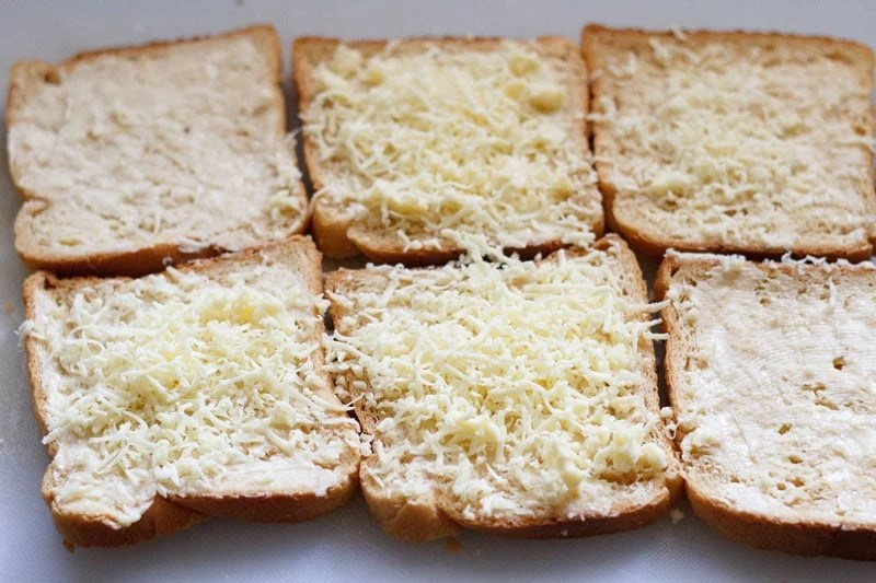 buttered bread slices topped with grated cheese