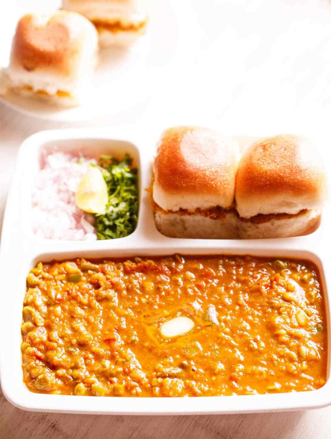 pav bhaji served in a rectangular serving tray with buttered pav and chopped onions, cilantro and lemon wedges
