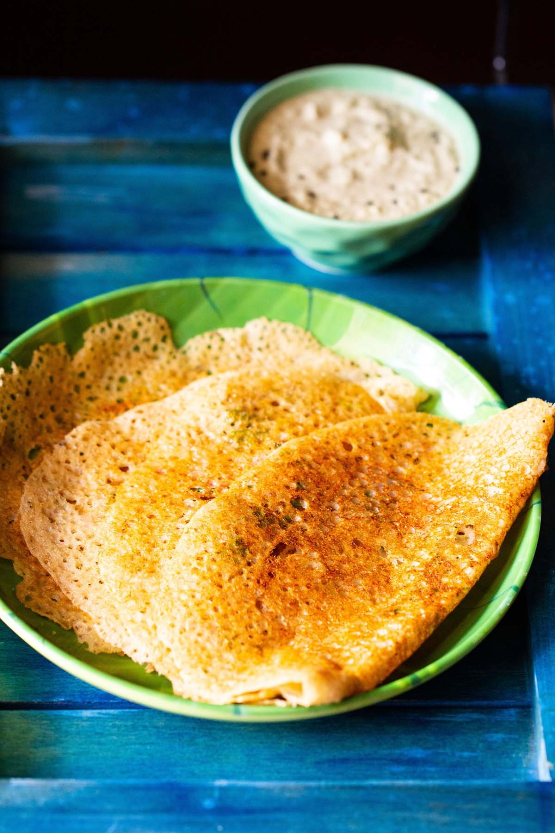 folded oats dosa placed on a green plate with a side of coconut chutney in a green bowl
