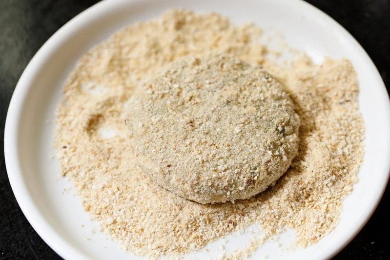 crumb coated cutlet on the breadcrumbs in white plate