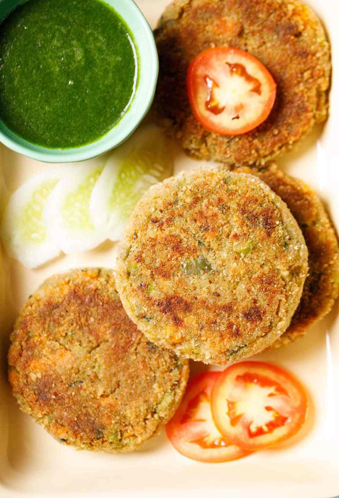 cutlets placed on a tray with a few slices of tomatoes, cucumber and a light green bowl filled with green chutney