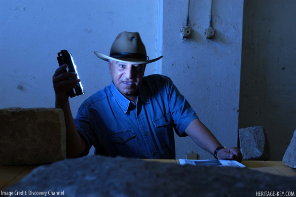 Dr. Zahi Hawass searching for stone block bearing clue to King Tut's parentage in a magazine at Ashmunein.
