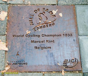 The road drifts right past the cemetery and on the pavement the names of previous champions are commemorated in iron.