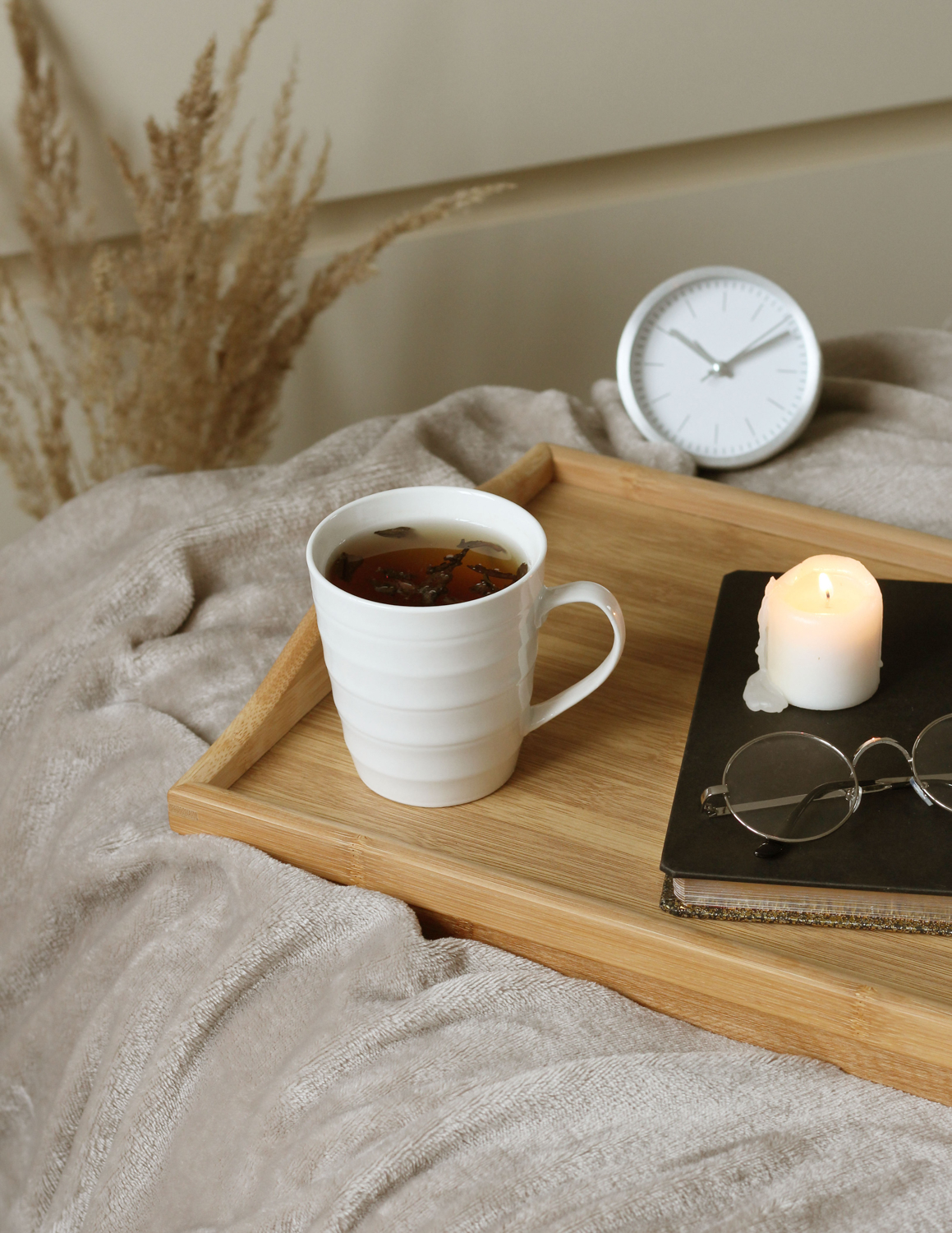 Wooden tray with a cup of tea and decor details on the bed with soft blanket.