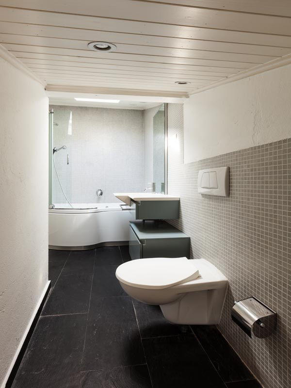 black tiles on the floor with cream mosaics on the wall