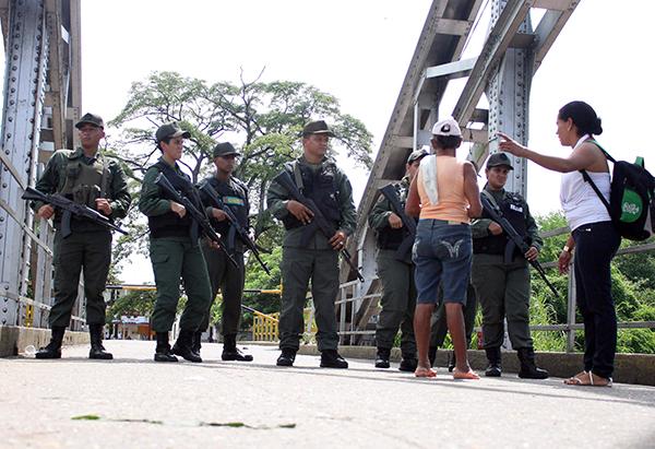 Ciudadanos colombianos hablan con guardias venezolanos en el Puente La Unión buscando pasar la frontera en Puerto Santander, Colombia. (EFE)