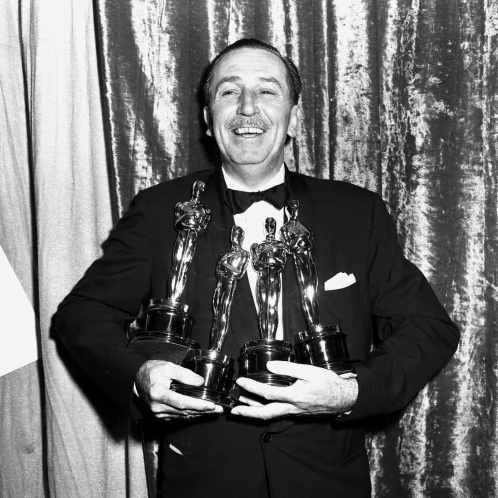 Walt Disney con quattro statuette degli Oscar.