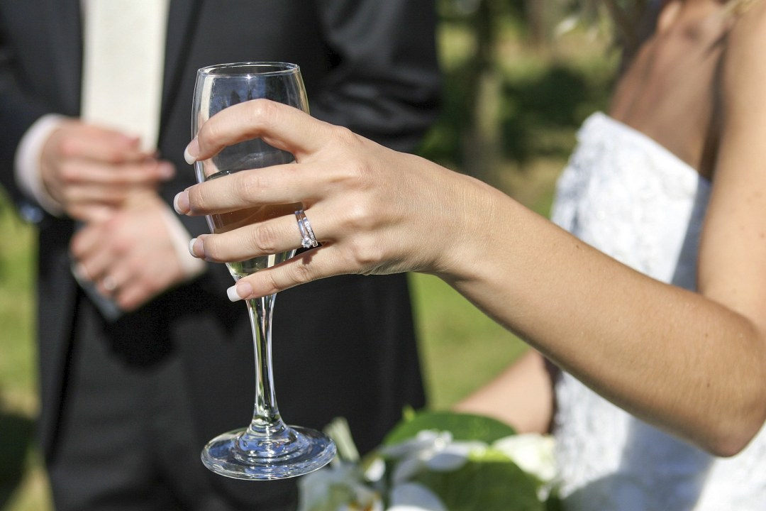 A woman showing off her wedding band holding champagne