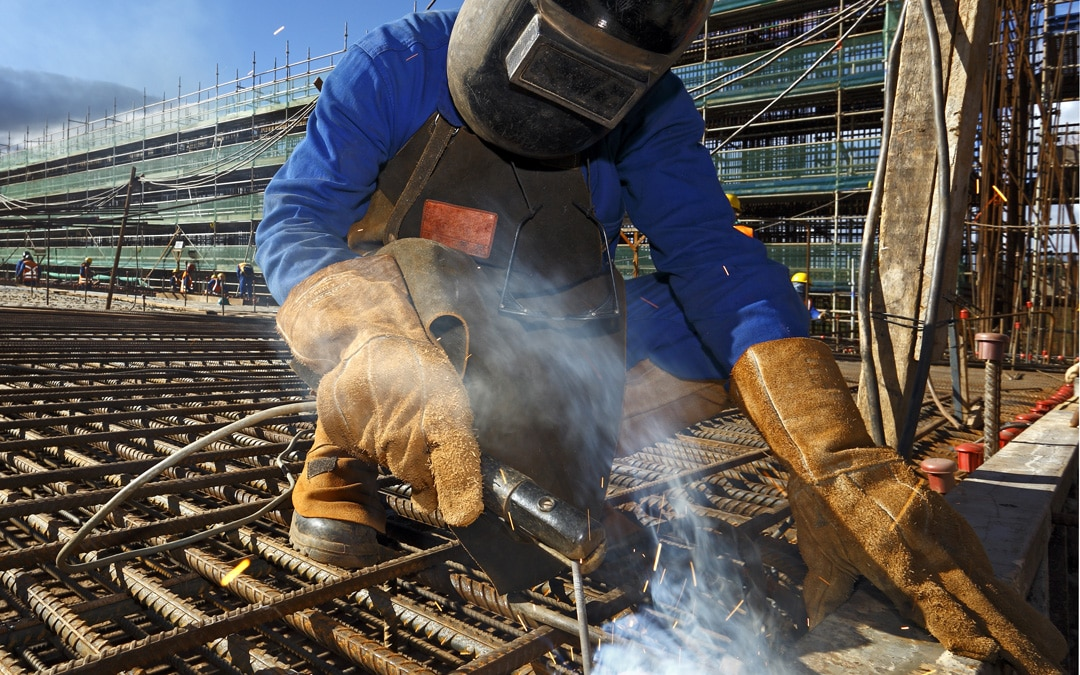 Person in protective gear welding a beam to a metal grid