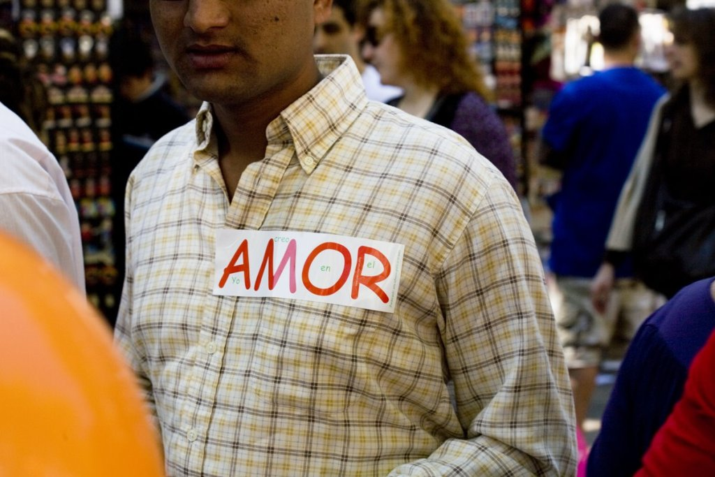 """Pakistanian man walking by """"Las Ramblas"""" with a love sticker on her shirt. Today is the day of the love in Barcelona."""